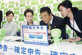 確定申告する俳優の高橋英樹さん(右から2人目)夫妻と長女真麻さん(左端)=18日午前、東京都港区の品川税務署