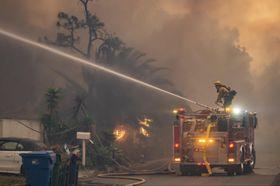 家屋への延焼を食い止めるために消火活動をする消防隊員=11日、米カリフォルニア州(UPI=共同)