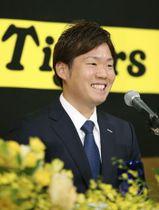 阪神の入団記者会見で笑顔を見せる西勇輝投手=14日午後、大阪市内のホテル