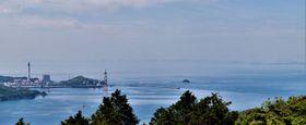 高効率化が発表された松島火力発電所(左)と洋上風力発電の「有望区域」に選定された江島沖(右端の海域)=西海市大瀬戸町、紫雲山から撮影