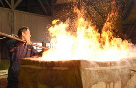 「日刀保たたら」の火入れ式で、激しく炎を上げる炉に砂鉄を入れる技師長=24日、島根県奥出雲町