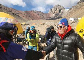 南米大陸最高峰アコンカグアのベースキャンプを先に出発する次男豪太さん(左)と握手する三浦雄一郎さん=17日(ミウラ・ドルフィンズ提供)