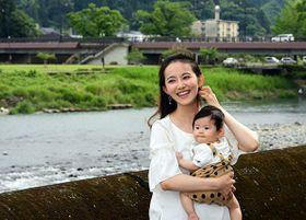 長男・宗一郎ちゃんとよく散歩するという球磨川沿いで笑顔をみせる吉松千晴さん=人吉市