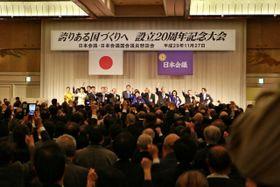 「日本会議設立20周年記念大会」で腰に手を当て拳を突き上げる参加者と登壇者ら=2017年11月27日、東京・港区の「東京プリンスホテル」