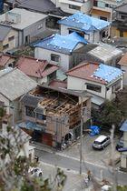 屋根が壊れたままの建物やブルーシートが張られた家屋が残る千葉県鋸南町の住宅街=22日午前