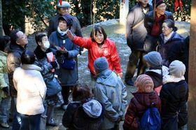 ツアー客に平家谷の歴史を説明する上田さん(中央)