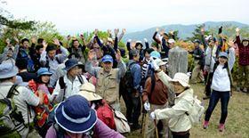 山頂で万歳三唱し、喜びを分かち合う登山客