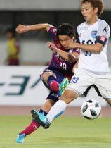 後半、シュートを放つファジアーノ岡山のFW仲間隼斗(左)=シティライトスタジアム