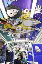 新装された列車内で、天井のイラストを見上げる乗客=20日、鳥取県米子市のJR米子駅