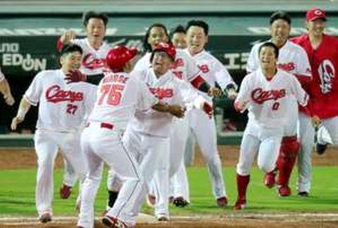サヨナラ勝ちで優勝へのマジックナンバーを1とし、サヨナラ打を放った松山(中央)へ駆け寄る広島ナイン(撮影・山崎亮)