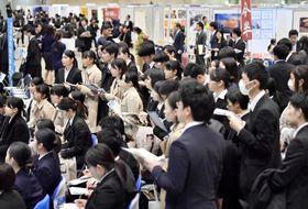 合同会社説明会のブースで話を聞く就職活動の学生=3月1日、千葉市の幕張メッセ