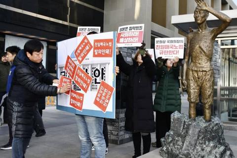 ソウル市内に設置された韓国人元徴用工を象徴する像の前で集会を開く労働団体 =2019年12月13日(共同)