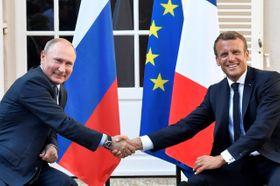 ブレガンソン城塞での首脳会談で握手を交わすマクロン大統領(右)とプーチン大統領=19日、ボルム・レ・ミモザ(ロイター=共同)