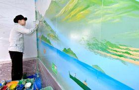 大正湯の浴場壁面に八幡浜の風景やマーマレードをイメージしたペンキ絵を描く田中さん