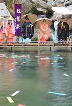熊野那智大社の紅葉祭で、色とりどりの短冊を「文覚の滝」に流す神職やみこら=14日、和歌山県那智勝浦町