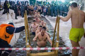 凍結した湖の氷をくりぬいた水の中で沐浴するロシア正教の信者ら=18日深夜、ロシア西部ニジニーノブゴロド(タス=共同)