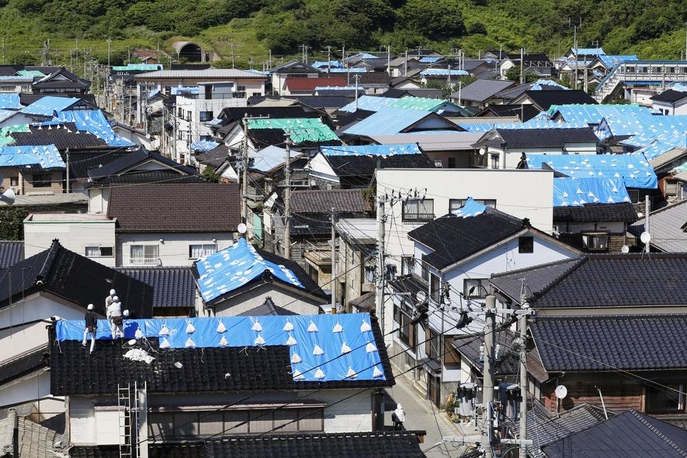 屋根がブルーシートで覆われ、復旧作業が続く山形県鶴岡市の住宅地=25日午後