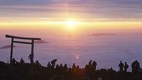 雲海から顔を出したオレンジ色に輝く御来光=11日午前4時40分、富士山頂