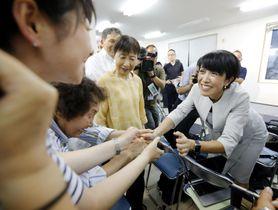秋田選挙区で当選を決め、支持者と握手する野党統一候補の無所属新人寺田静氏(右)=21日夜、秋田市