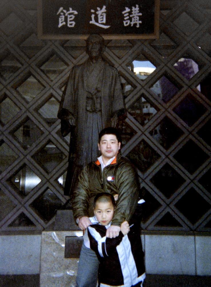 講道館の前で父親の安泰範さん(上)と記念写真に納まる初級学校時代の安昌林=東京都文京区