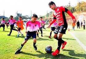子供と笑顔でサッカーをするチャナティップ(手前右)=中川明紀撮影