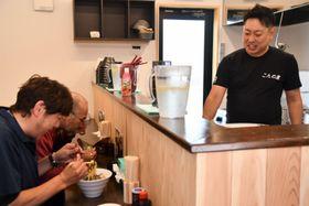 チャレンジショップに出店し、ラーメンを提供する紺野学さん(右)