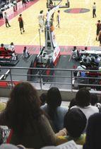 バスケットボール男子Bリーグの試合を観戦する遺児(手前右)と保護者の女性(左)=22日午後、東京都立川市