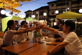 「乾杯!」。野外でビールを楽しむ観光客ら=雲仙市、雲仙温泉街