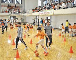 鈴木さん(手前左)や福西さん(同左から3人目)ら元日本代表選手と練習する子どもたち=鯖江市総合体育館で