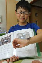 採集した虫の「レア度」を書いたノートと、キンオニクワガタを見せる浦谷君=長崎県対馬市厳原町の自宅