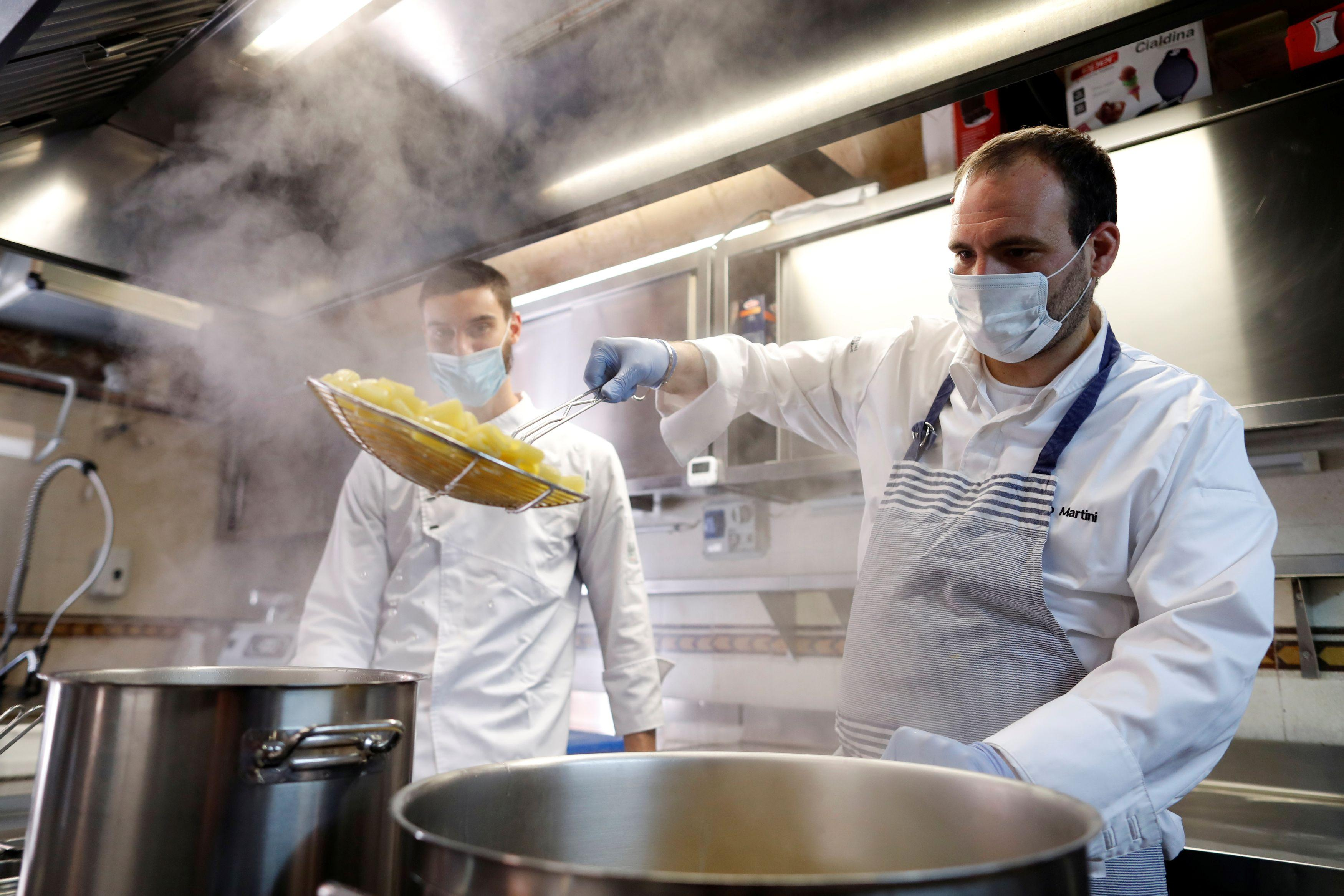 ローマで営業再開を前に衛生規則確認のためランチを作るレストランのオーナー=15日(ロイター=共同)