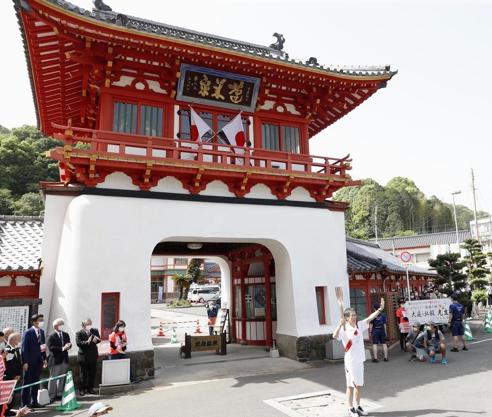 佐賀県武雄市のゴール地点「武雄温泉楼門」に到着した聖火ランナー=9日午後