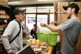 買い物に来た外国人(左)と店内で話す松本さん