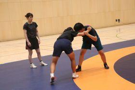 【練習する選手を見守る吉田さん(左)=津市北河路町のサオリーナで】