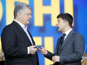 19日、ウクライナ・キエフのスタジアムで行われた討論会で議論するポロシェンコ大統領(左)とゼレンスキー氏(AP=共同)