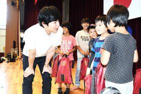 小学校で避難生活を送る子どもと交流する松本潤さん(左)=21日午前8時35分ごろ、西予市野村町野村