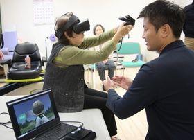 永山さん(右)の説明を受けながら、VRを使ったリハビリに取り組む施設利用者=長崎市、ショートステイ王樹
