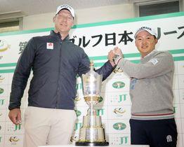 記者会見前に握手を交わす今平周吾(右)とショーン・ノリス=4日、東京よみうりCC