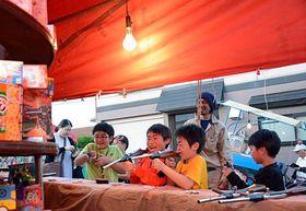 弘前市内のトップを切って行われた「山観の宵宮」で射的を楽しむ子どもたち