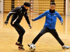 初練習でボールを奪い合うFW谷口海斗(左)とGK土井康平=盛岡市・盛岡タカヤアリーナ