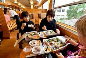 観光列車「はやとの風」で、フレンチ弁当を食べるツアー参加者=JR小林駅