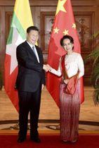 ミャンマー・ネピドーで、中国の習近平国家主席(左)と会談前に握手するアウン・サン・スー・チー国家顧問兼外相=18日(ミャンマー政府提供・共同)