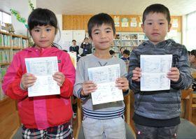 配布された読書通帳を手にする児童たち