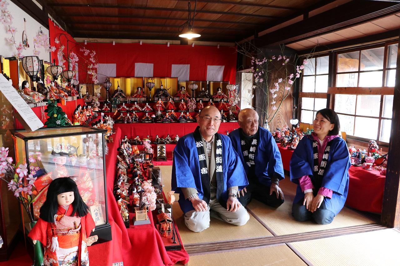 ずらりと並んだひな人形に囲まれて話す村川一恵会長(右端)ら松原宿活性化協議会のメンバー=2019年3月、長崎県大村市