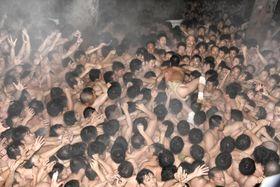 熱気で湯気が立ち上る中、奇祭「西大寺会陽」で投下された宝木を奪い合う男たち=17日夜、岡山市の西大寺観音院