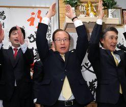 4選を確実にし、万歳で喜ぶ朝長則男氏(中央)=21日午後8時17分、佐世保市下京町の選挙事務所