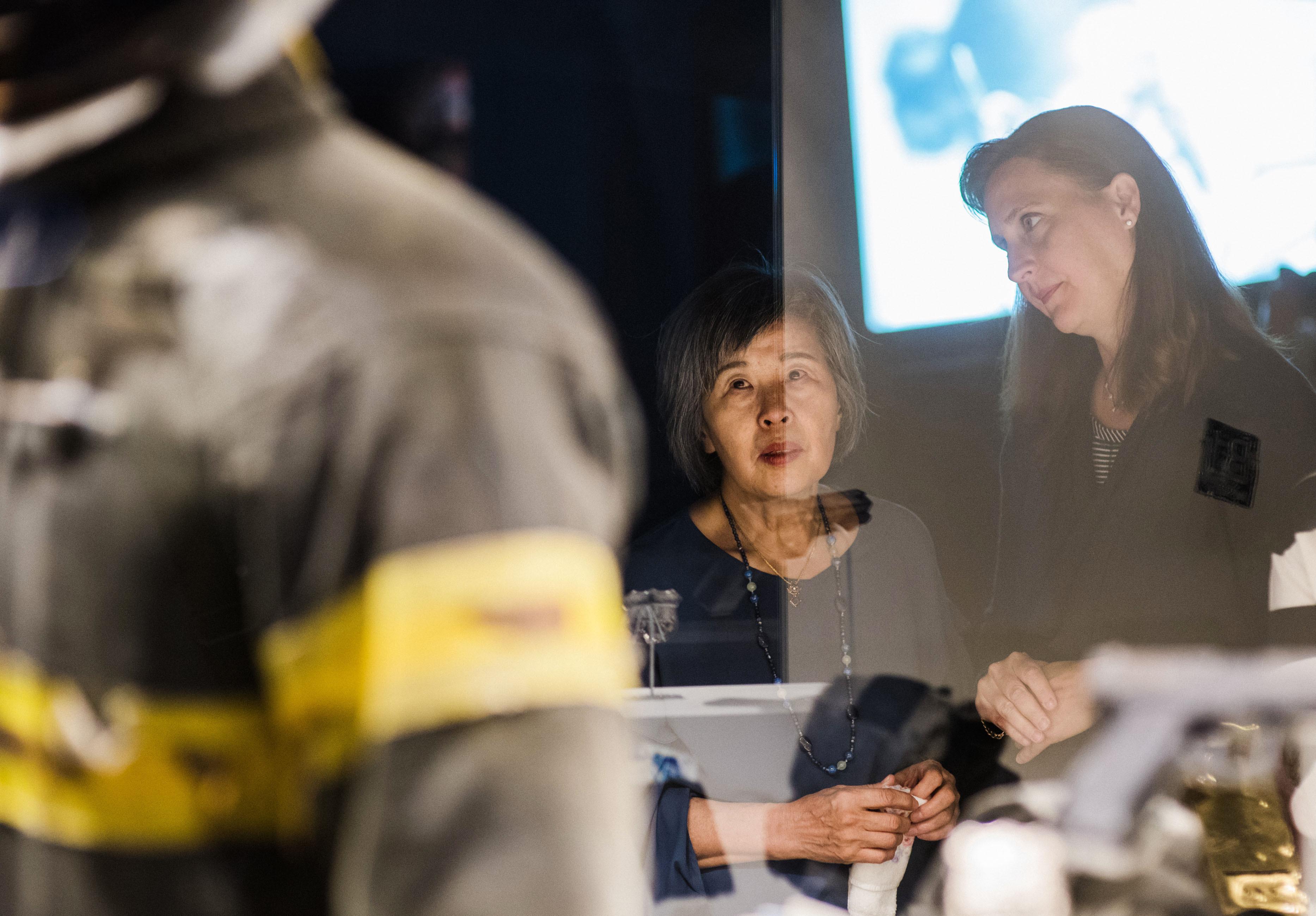 「9・11トリビュート博物館」でリー・イエルピ家族会会長の息子ジョナサンの遺品に言葉を失う高橋シズヱ(左)。消防服の背中は大きく裂けており、同時テロのビル倒壊の激しさを物語っていた=米ニューヨーク(撮影・ライアン・クリストファー・ジョーンズ、共同)
