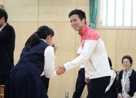 特別授業後に生徒らと笑顔で握手を交わす小山さん=川崎市麻生区の市立西生田中