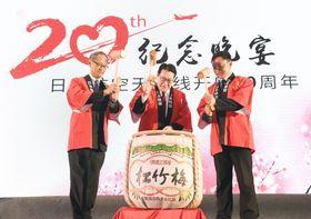 日本航空の名古屋―天津路線の開設20年を記念する式典で鏡開きをする植木義晴会長(中央)ら=19日、中国・天津(共同)