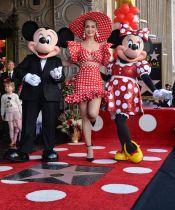 22日、米ハリウッドでのセレモニーに参加したミニー(右)やポップ歌手のケイティ・ペリーさん(中央)ら(UPI=共同)